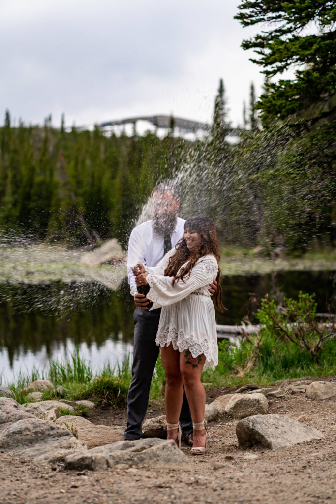 An engaged couple dressed in white doing a champagne toast in front of a beautiful lake in Colorado. Photo by Gabby Jockers Photography. brainard lake engagement photography, brainard lake engagement photos, brainard lake engagement session, colorado engagement photos, colorado engagement session, colorado photography, mountain, engagement photos, sunset engagement session, hiking engagement, adventure photos, adventure session, couples photos, blue hour photos