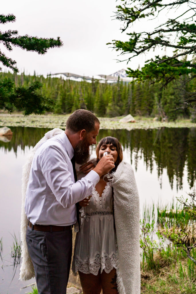 An engaged couple enjoying some champagne while wrapped in a blanket against the cold in front of a lake in the woods. Photo by Gabby Jockers Photography. brainard lake engagement photography, brainard lake engagement photos, brainard lake engagement session, colorado engagement photos, colorado engagement session, colorado photography, mountain, engagement photos, sunset engagement session, hiking engagement, adventure photos, adventure session, couples photos, blue hour photos