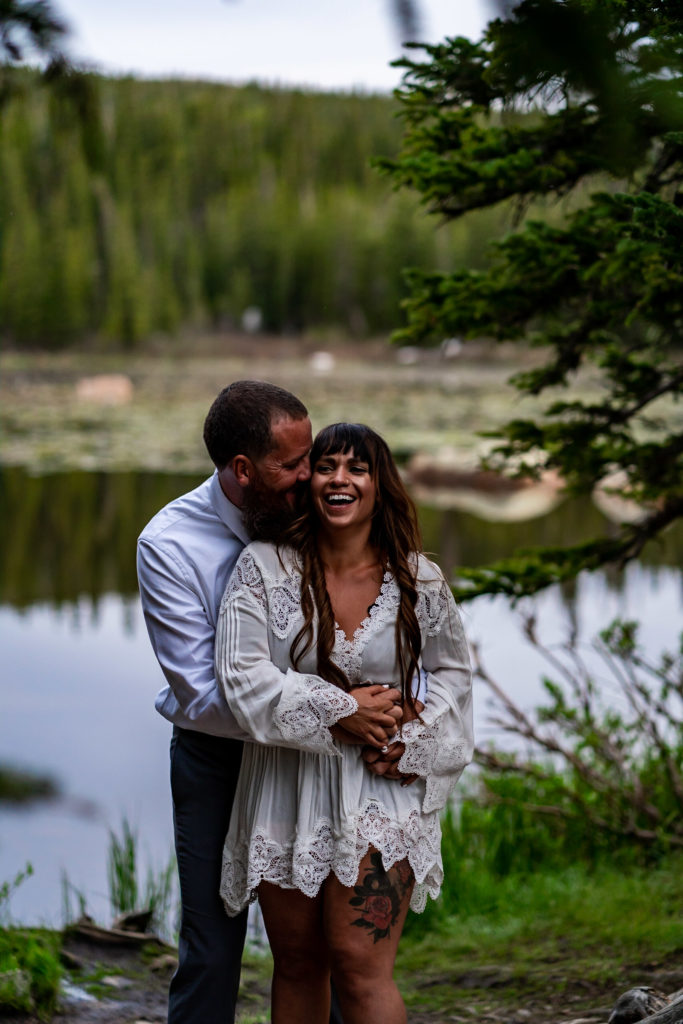 A laughing embrace between an engaged couple in front of a lake in the woods in Colorado. Photo by Gabby Jockers Photography. brainard lake engagement photography, brainard lake engagement photos, brainard lake engagement session, colorado engagement photos, colorado engagement session, colorado photography, mountain, engagement photos, sunset engagement session, hiking engagement, adventure photos, adventure session, couples photos, blue hour photos