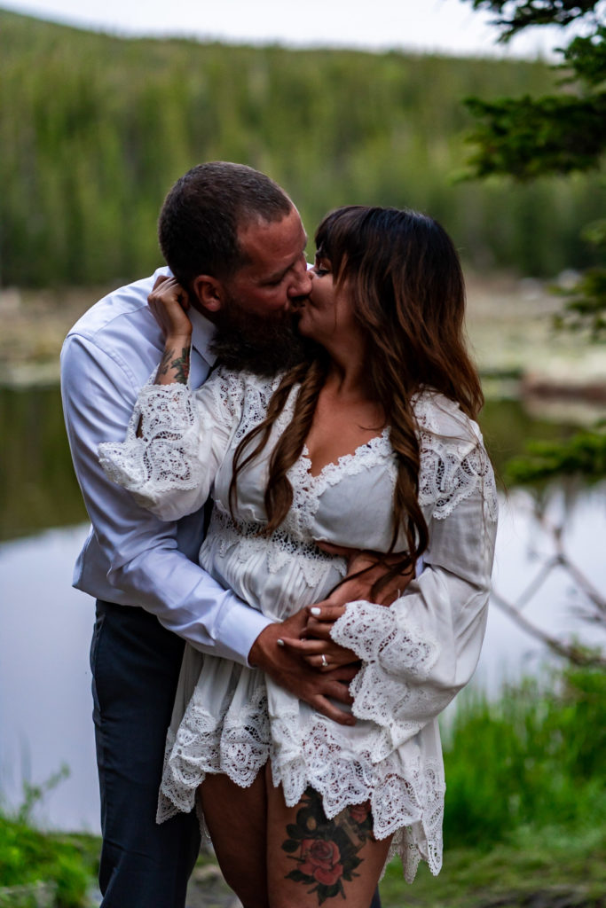 A passionate embrace between an engaged couple in front of a lake in the woods in Colorado. Photo by Gabby Jockers Photography. brainard lake engagement photography, brainard lake engagement photos, brainard lake engagement session, colorado engagement photos, colorado engagement session, colorado photography, mountain, engagement photos, sunset engagement session, hiking engagement, adventure photos, adventure session, couples photos, blue hour photos