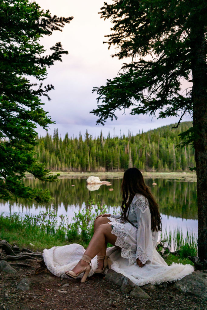 A woman sitting on a white blanket overlooking a lake in the woods. Photo by Gabby Jockers Photography. brainard lake engagement photography, brainard lake engagement photos, brainard lake engagement session, colorado engagement photos, colorado engagement session, colorado photography, mountain, engagement photos, sunset engagement session, hiking engagement, adventure photos, adventure session, couples photos, blue hour photos