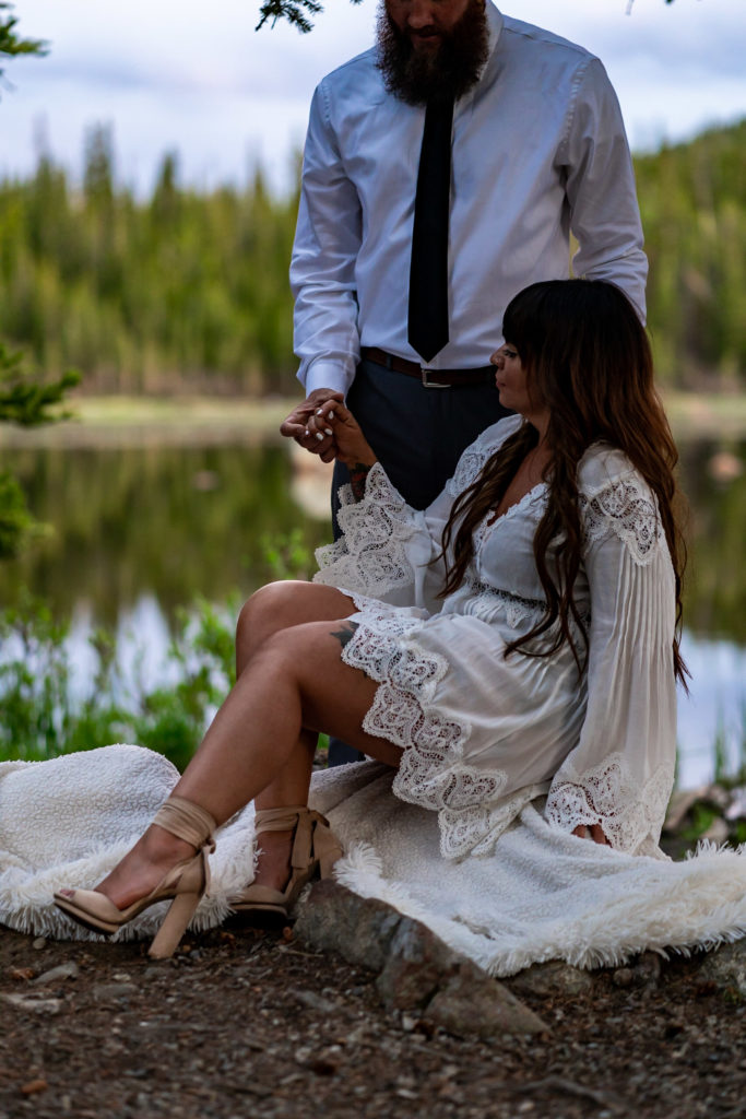 A woman sitting on a white blanket while a man stands behind her holding her hand, both in front of a lake in the woods. Photo by Gabby Jockers Photography. brainard lake engagement photography, brainard lake engagement photos, brainard lake engagement session, colorado engagement photos, colorado engagement session, colorado photography, mountain, engagement photos, sunset engagement session, hiking engagement, adventure photos, adventure session, couples photos, blue hour photos