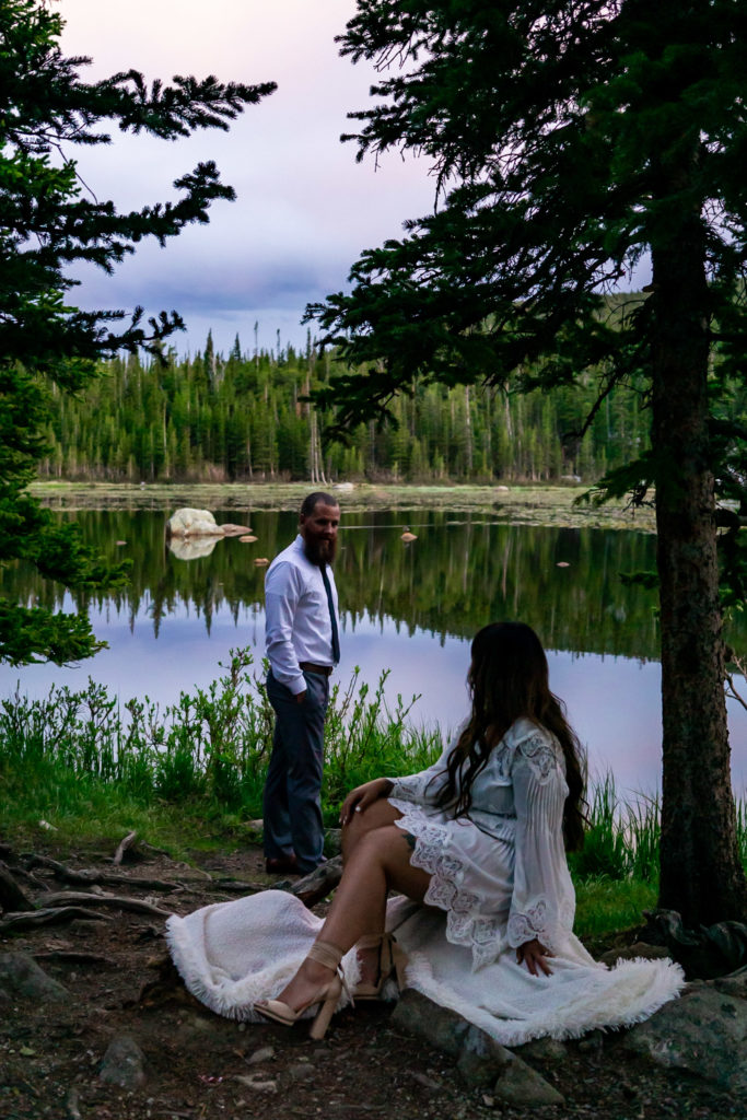 A couple looking at each other over space in front of a lake in the woods. Photo by Gabby Jockers Photography. brainard lake engagement photography, brainard lake engagement photos, brainard lake engagement session, colorado engagement photos, colorado engagement session, colorado photography, mountain, engagement photos, sunset engagement session, hiking engagement, adventure photos, adventure session, couples photos, blue hour photos