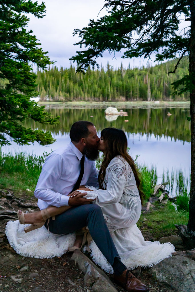 A couple sitting snuggled together in front of a lake in the woods. Photo by Gabby Jockers Photography. brainard lake engagement photography, brainard lake engagement photos, brainard lake engagement session, colorado engagement photos, colorado engagement session, colorado photography, mountain, engagement photos, sunset engagement session, hiking engagement, adventure photos, adventure session, couples photos, blue hour photos