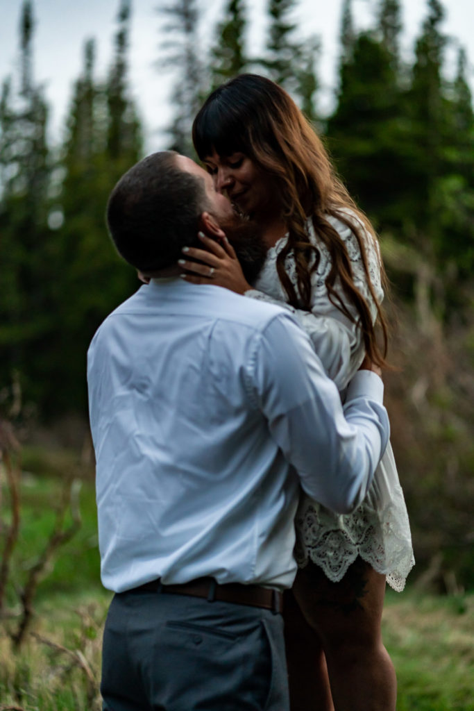 A man standing in front of his fiance holding on to her as they kiss. Photo by Gabby Jockers Photography. brainard lake engagement photography, brainard lake engagement photos, brainard lake engagement session, colorado engagement photos, colorado engagement session, colorado photography, mountain, engagement photos, sunset engagement session, hiking engagement, adventure photos, adventure session, couples photos, blue hour photos