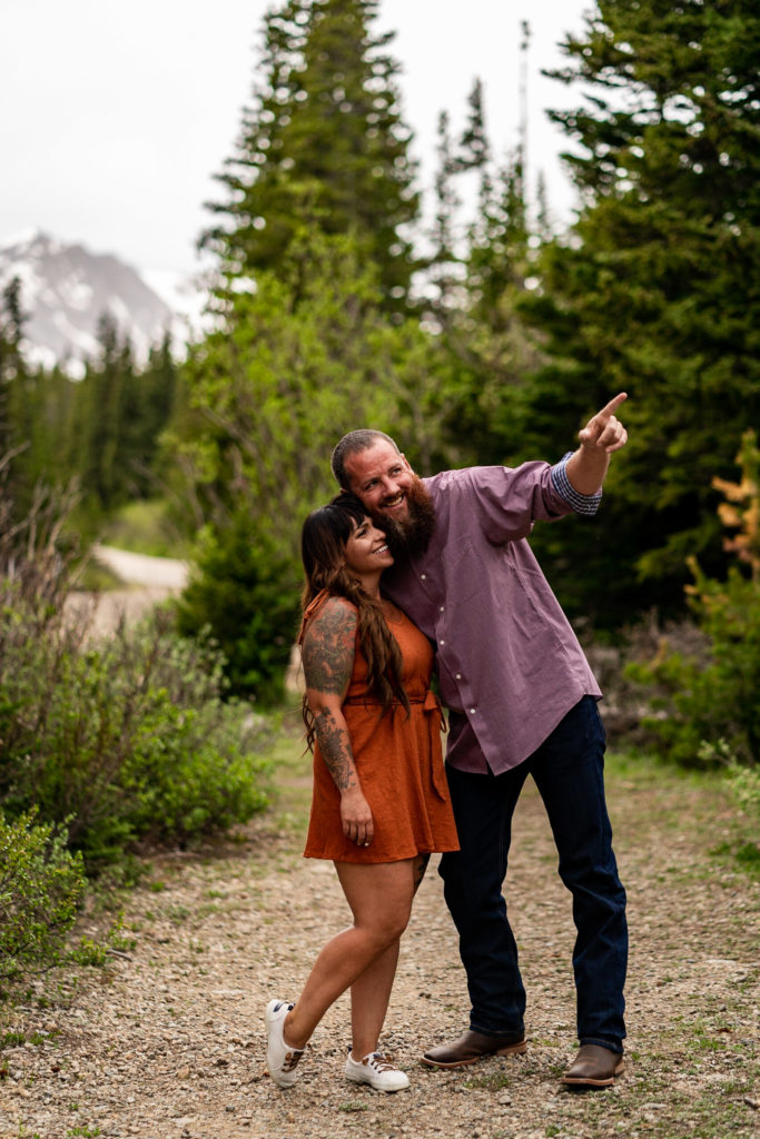 A couple hanging out in the woods in front of a mountain in Colorado. Photo by Gabby Jockers Photography. brainard lake engagement photography, brainard lake engagement photos, brainard lake engagement session, colorado engagement photos, colorado engagement session, colorado photography, mountain, engagement photos, sunset engagement session, hiking engagement, adventure photos, adventure session, couples photos, blue hour photos