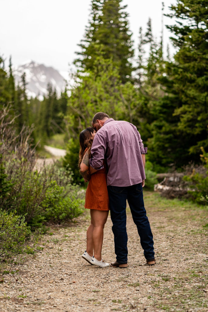 A couple kissing in the woods in front of a mountain in Colorado. Photo by Gabby Jockers Photography. brainard lake engagement photography, brainard lake engagement photos, brainard lake engagement session, colorado engagement photos, colorado engagement session, colorado photography, mountain, engagement photos, sunset engagement session, hiking engagement, adventure photos, adventure session, couples photos, blue hour photos