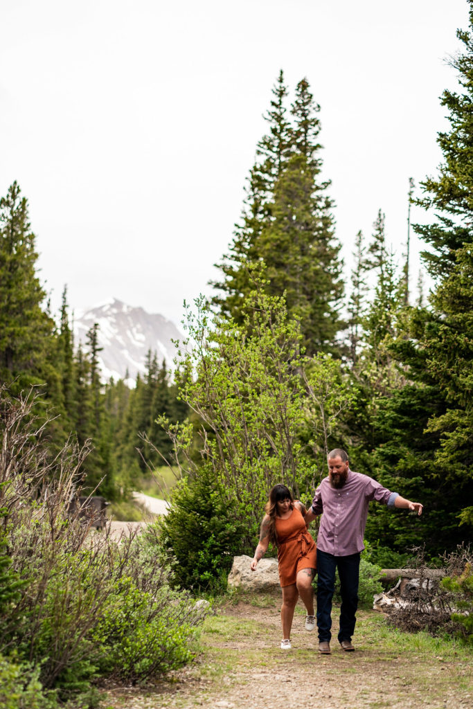 A couple bumping hips in the woods in front of a mountain in Colorado. Photo by Gabby Jockers Photography. brainard lake engagement photography, brainard lake engagement photos, brainard lake engagement session, colorado engagement photos, colorado engagement session, colorado photography, mountain, engagement photos, sunset engagement session, hiking engagement, adventure photos, adventure session, couples photos, blue hour photos