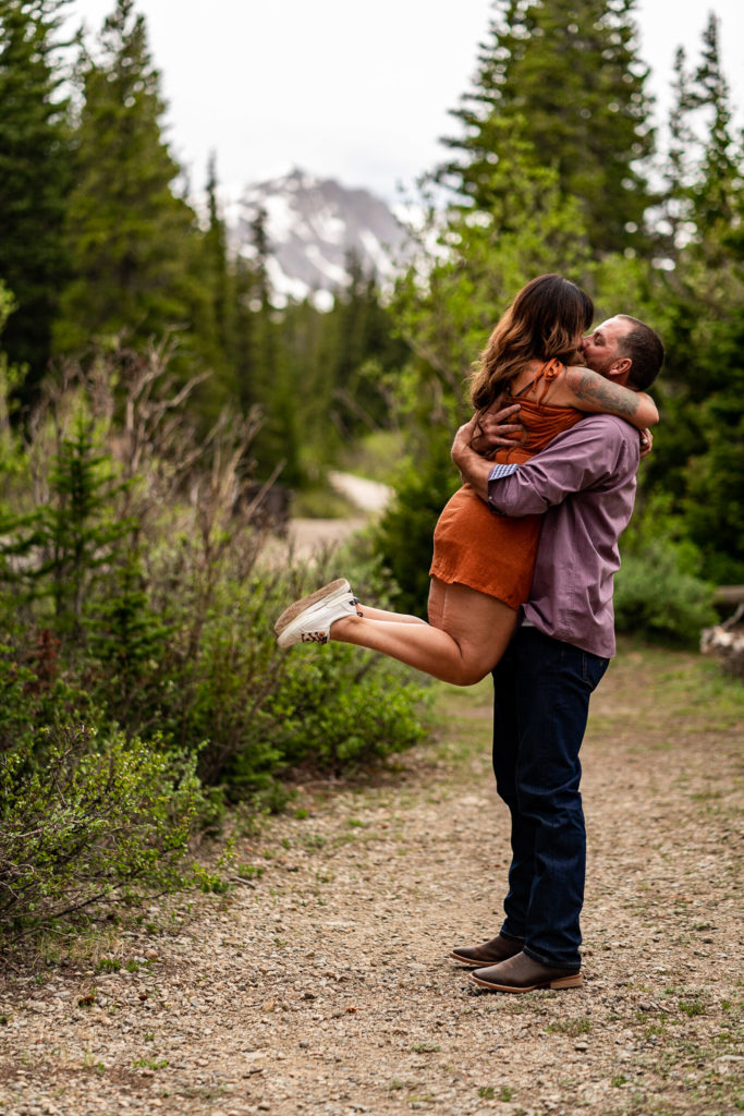 A man holding his fiance up in the air in front of a beautiful mountain while they kiss. Photo by Gabby Jockers Photography. brainard lake engagement photography, brainard lake engagement photos, brainard lake engagement session, colorado engagement photos, colorado engagement session, colorado photography, mountain, engagement photos, sunset engagement session, hiking engagement, adventure photos, adventure session, couples photos, blue hour photos