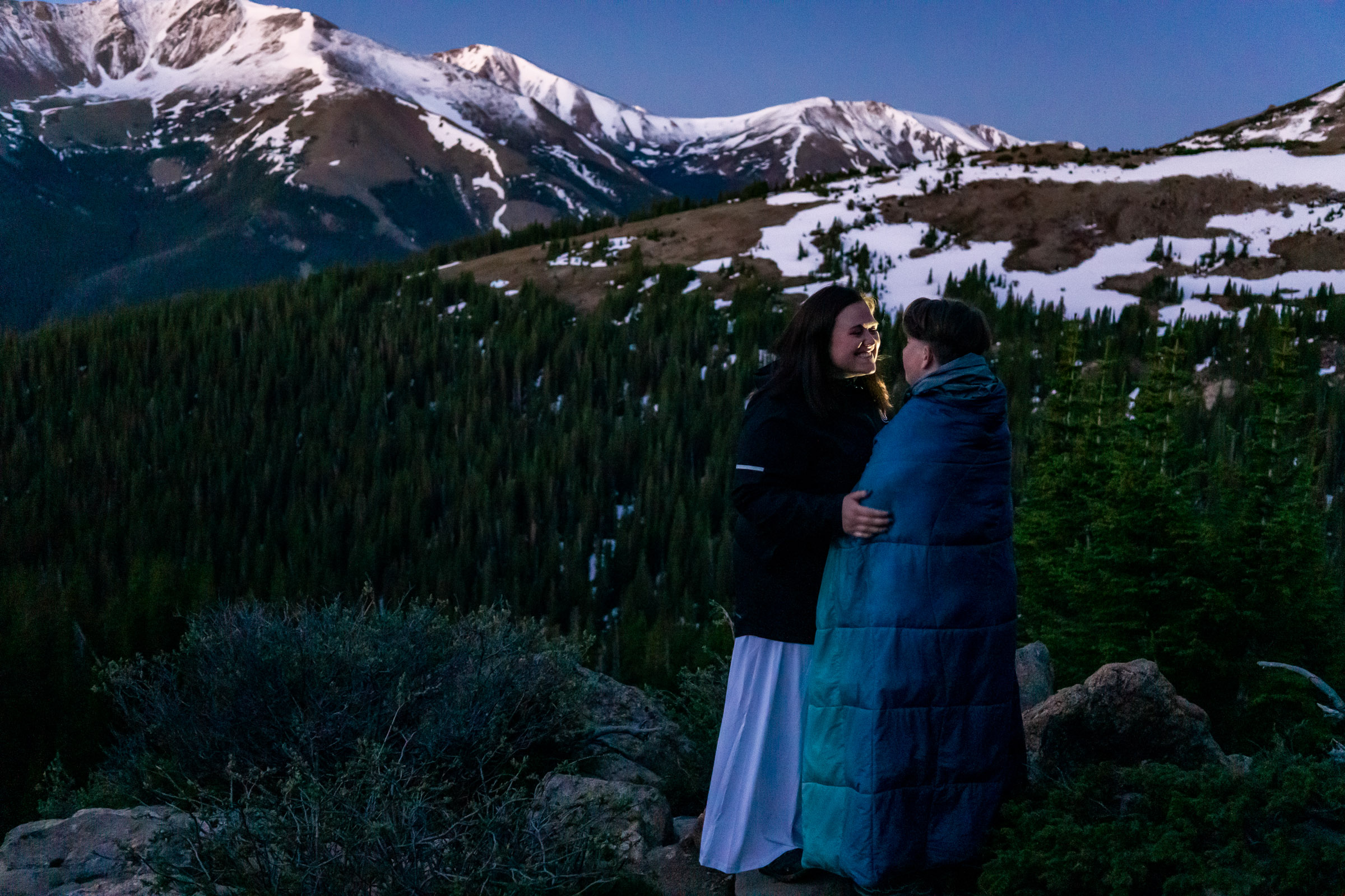 Two brides happily embracing in front of a mountain alpenglow sunrise. Photo by Gabby Jockers Photography. Same sex wedding, lesbian elopement, lesbian wedding, lgbt elopement, lgbtqia wedding, lgbt wedding, colorado elopement, colorado elopement photography, berthoud pass, sunrise elopement, hiking elopement, spring wedding, mountain wedding, adventure photos, mountain elopement, spring elopement, adventure elopement, denver colorado photographer, elopement photographer