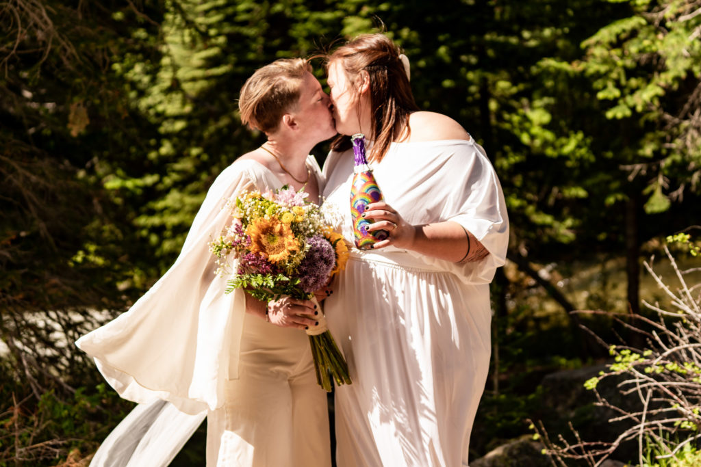 Two brides celebrating their wedding with a bottle of pride champagne and sunflower bouquet. Photo by Gabby Jockers Photography. Same sex wedding, lesbian elopement, lesbian wedding, lgbt elopement, lgbtqia wedding, lgbt wedding, colorado elopement, colorado elopement photography, berthoud pass, sunrise elopement, hiking elopement, spring wedding, mountain wedding, adventure photos, mountain elopement, spring elopement, adventure elopement, denver colorado photographer, elopement photographer