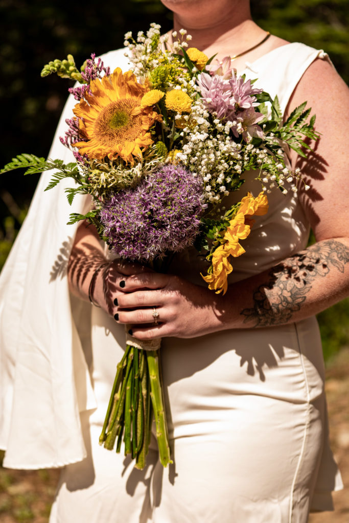 A bride in a wedding jumpsuit holding a colorful sunflower bouquet. Photo by Gabby Jockers Photography. Same sex wedding, lesbian elopement, lesbian wedding, lgbt elopement, lgbtqia wedding, lgbt wedding, colorado elopement, colorado elopement photography, berthoud pass, sunrise elopement, hiking elopement, spring wedding, mountain wedding, adventure photos, mountain elopement, spring elopement, adventure elopement, denver colorado photographer, elopement photographer