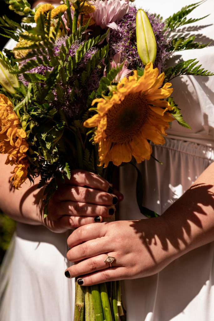 A bride holding a colorful sunflower bouquet. Photo by Gabby Jockers Photography. Same sex wedding, lesbian elopement, lesbian wedding, lgbt elopement, lgbtqia wedding, lgbt wedding, colorado elopement, colorado elopement photography, berthoud pass, sunrise elopement, hiking elopement, spring wedding, mountain wedding, adventure photos, mountain elopement, spring elopement, adventure elopement, denver colorado photographer, elopement photographer