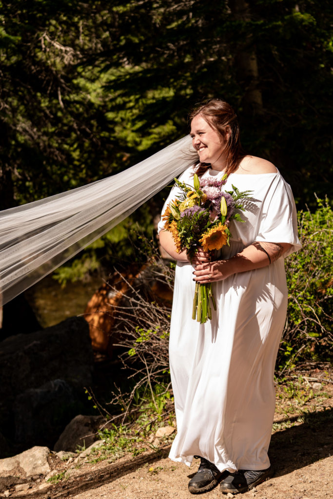 A bride smiling with her extra-long veil blowing in the wind, holding a colorful bouquet. Photo by Gabby Jockers Photography. Same sex wedding, lesbian elopement, lesbian wedding, lgbt elopement, lgbtqia wedding, lgbt wedding, colorado elopement, colorado elopement photography, berthoud pass, sunrise elopement, hiking elopement, spring wedding, mountain wedding, adventure photos, mountain elopement, spring elopement, adventure elopement, denver colorado photographer, elopement photographer