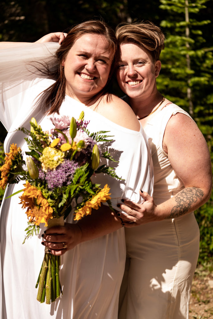 Two beautiful brides in white cuddling and smiling at the camera with a colorful summer bouquet. Photo by Gabby Jockers Photography. Same sex wedding, lesbian elopement, lesbian wedding, lgbt elopement, lgbtqia wedding, lgbt wedding, colorado elopement, colorado elopement photography, berthoud pass, sunrise elopement, hiking elopement, spring wedding, mountain wedding, adventure photos, mountain elopement, spring elopement, adventure elopement, denver colorado photographer, elopement photographer