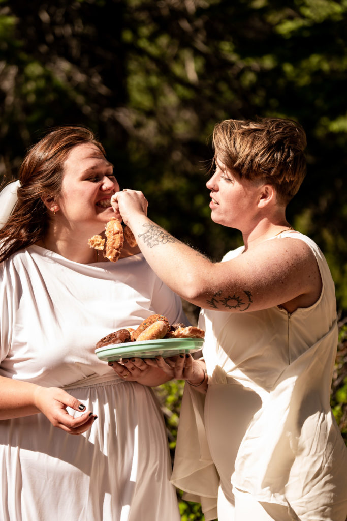 Two brides outside in nature enjoying donuts instead of cake on their wedding day. Photo by Gabby Jockers Photography. Same sex wedding, lesbian elopement, lesbian wedding, lgbt elopement, lgbtqia wedding, lgbt wedding, colorado elopement, colorado elopement photography, berthoud pass, sunrise elopement, hiking elopement, spring wedding, mountain wedding, adventure photos, mountain elopement, spring elopement, adventure elopement, denver colorado photographer, elopement photographer