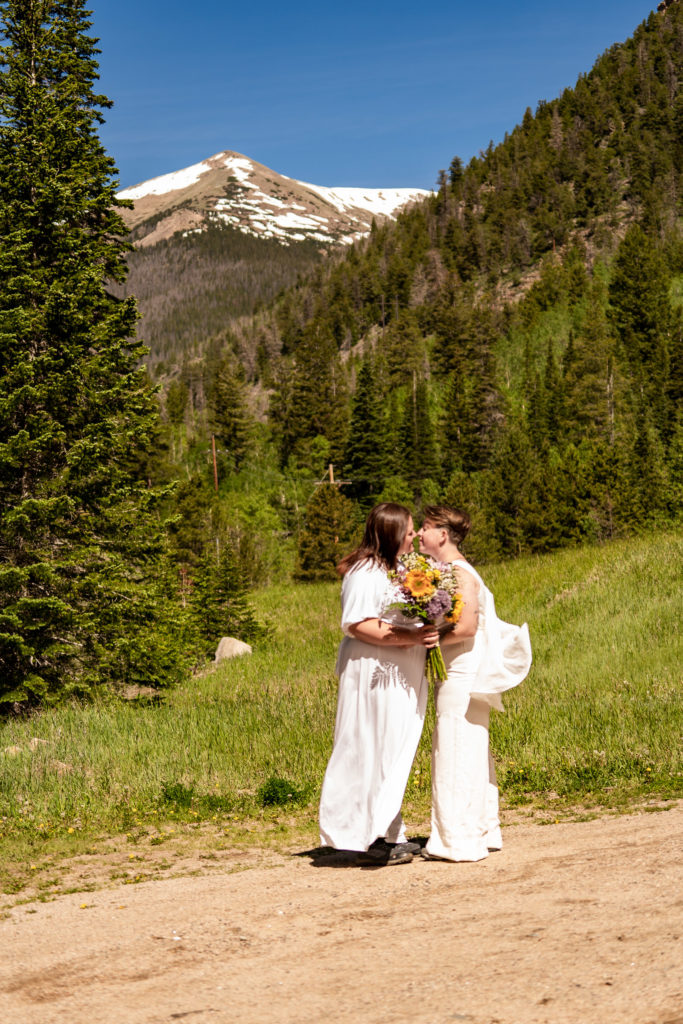 Two brides kissing in front of a beautiful Colorado mountain. Photo by Gabby Jockers Photography. Same sex wedding, lesbian elopement, lesbian wedding, lgbt elopement, lgbtqia wedding, lgbt wedding, colorado elopement, colorado elopement photography, berthoud pass, sunrise elopement, hiking elopement, spring wedding, mountain wedding, adventure photos, mountain elopement, spring elopement, adventure elopement, denver colorado photographer, elopement photographer
