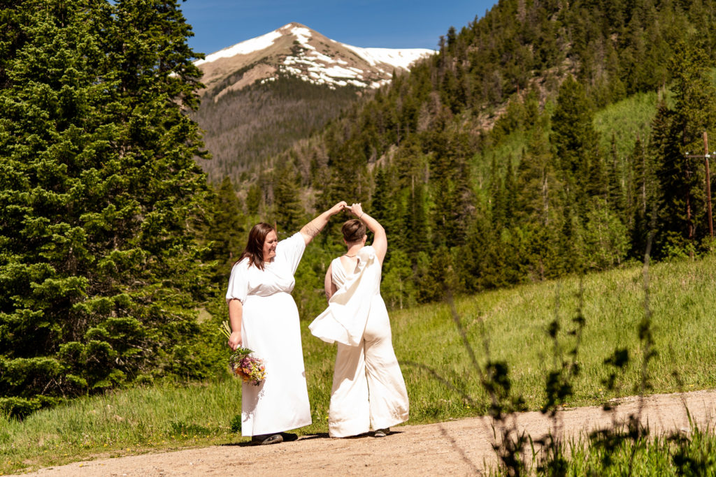 Two women in bridal outfits in front of a mountain. One woman is twirling the other. Photo by Gabby Jockers Photography. Same sex wedding, lesbian elopement, lesbian wedding, lgbt elopement, lgbtqia wedding, lgbt wedding, colorado elopement, colorado elopement photography, berthoud pass, sunrise elopement, hiking elopement, spring wedding, mountain wedding, adventure photos, mountain elopement, spring elopement, adventure elopement, denver colorado photographer, elopement photographer