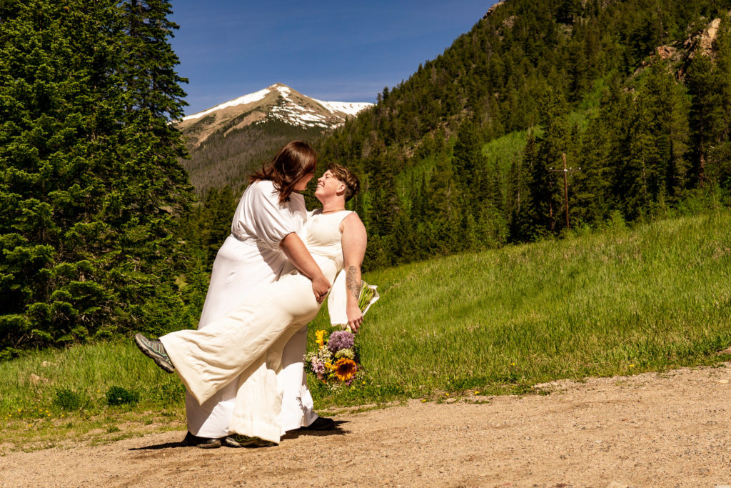 Two women in bridal outfits in front of a mountain. One woman is dipping the other for a kiss. Photo by Gabby Jockers Photography. Same sex wedding, lesbian elopement, lesbian wedding, lgbt elopement, lgbtqia wedding, lgbt wedding, colorado elopement, colorado elopement photography, berthoud pass, sunrise elopement, hiking elopement, spring wedding, mountain wedding, adventure photos, mountain elopement, spring elopement, adventure elopement, denver colorado photographer, elopement photographer