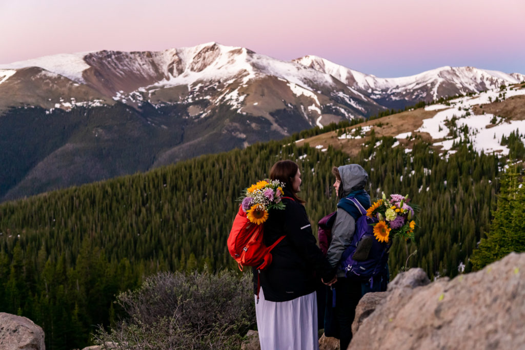 Two brides with bouquets sticking out of their backpacks embracing in front of a mountain alpenglow sunrise. Photo by Gabby Jockers Photography. Same sex wedding, lesbian elopement, lesbian wedding, lgbt elopement, lgbtqia wedding, lgbt wedding, colorado elopement, colorado elopement photography, berthoud pass, sunrise elopement, hiking elopement, spring wedding, mountain wedding, adventure photos, mountain elopement, spring elopement, adventure elopement, denver colorado photographer, elopement photographer