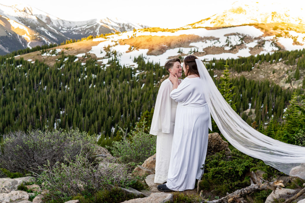 Two brides cuddling happily after sunrise in front of a mountain backdrop. Photo by Gabby Jockers Photography. Sunflower bouquet, Wedding jumpsuit, Same sex wedding, lesbian elopement, lesbian wedding, lgbt elopement, lgbtqia wedding, lgbt wedding, colorado elopement, colorado elopement photography, berthoud pass, sunrise elopement, hiking elopement, spring wedding, mountain wedding, adventure photos, mountain elopement, spring elopement, adventure elopement, denver colorado photographer, elopement photographer
