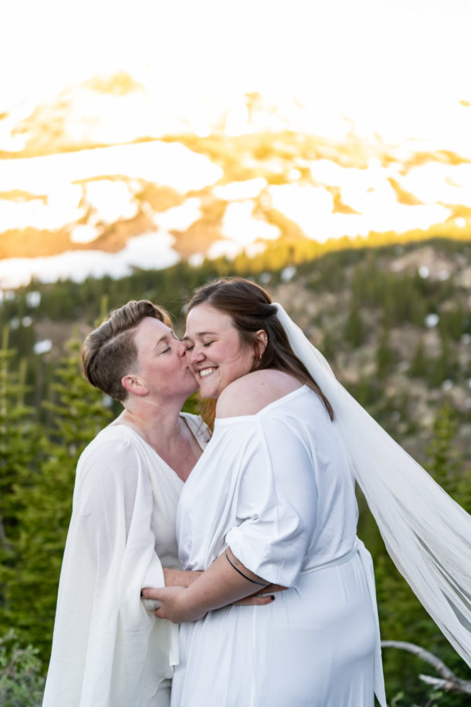 Two brides kissing in front of a mountain backdrop. Photo by Gabby Jockers Photography. Sunflower bouquet, Wedding jumpsuit, Same sex wedding, lesbian elopement, lesbian wedding, lgbt elopement, lgbtqia wedding, lgbt wedding, colorado elopement, colorado elopement photography, berthoud pass, sunrise elopement, hiking elopement, spring wedding, mountain wedding, adventure photos, mountain elopement, spring elopement, adventure elopement, denver colorado photographer, elopement photographer