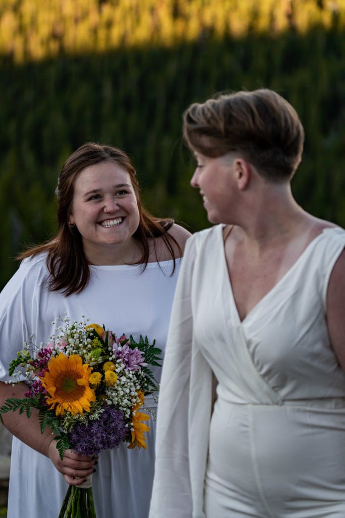 Two brides holding colorful sunflower bouquets in front of a mountain backdrop. Photo by Gabby Jockers Photography. Sunflower bouquet, Wedding jumpsuit, Same sex wedding, lesbian elopement, lesbian wedding, lgbt elopement, lgbtqia wedding, lgbt wedding, colorado elopement, colorado elopement photography, berthoud pass, sunrise elopement, hiking elopement, spring wedding, mountain wedding, adventure photos, mountain elopement, spring elopement, adventure elopement, denver colorado photographer, elopement photographer