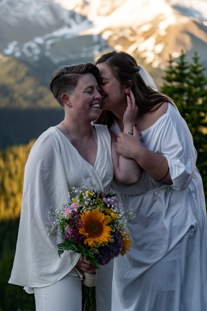 Two brides holding colorful sunflower bouquets in front of a mountain backdrop.Photo by Gabby Jockers Photography. Sunflower bouquet, Wedding jumpsuit, Same sex wedding, lesbian elopement, lesbian wedding, lgbt elopement, lgbtqia wedding, lgbt wedding, colorado elopement, colorado elopement photography, berthoud pass, sunrise elopement, hiking elopement, spring wedding, mountain wedding, adventure photos, mountain elopement, spring elopement, adventure elopement, denver colorado photographer, elopement photographer