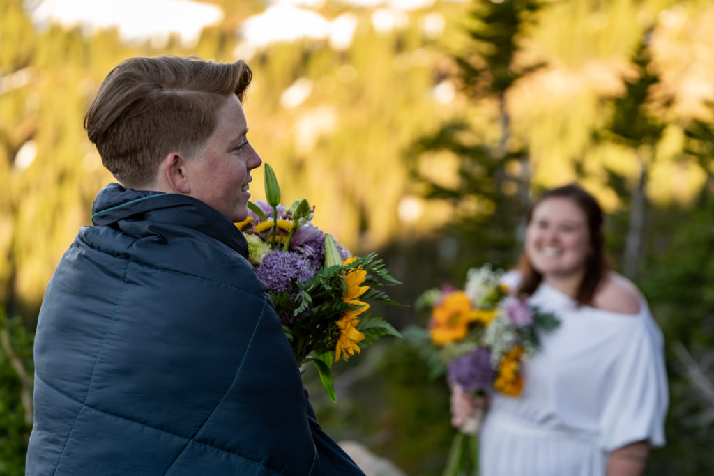 Two brides holding colorful sunflower bouquets in front of a mountain backdrop. One of them is snuggled up in a blanket. Photo by Gabby Jockers Photography. Same sex wedding, lesbian elopement, lesbian wedding, lgbt elopement, lgbtqia wedding, lgbt wedding, colorado elopement, colorado elopement photography, berthoud pass, sunrise elopement, hiking elopement, spring wedding, mountain wedding, adventure photos, mountain elopement, spring elopement, adventure elopement, denver colorado photographer, elopement photographer