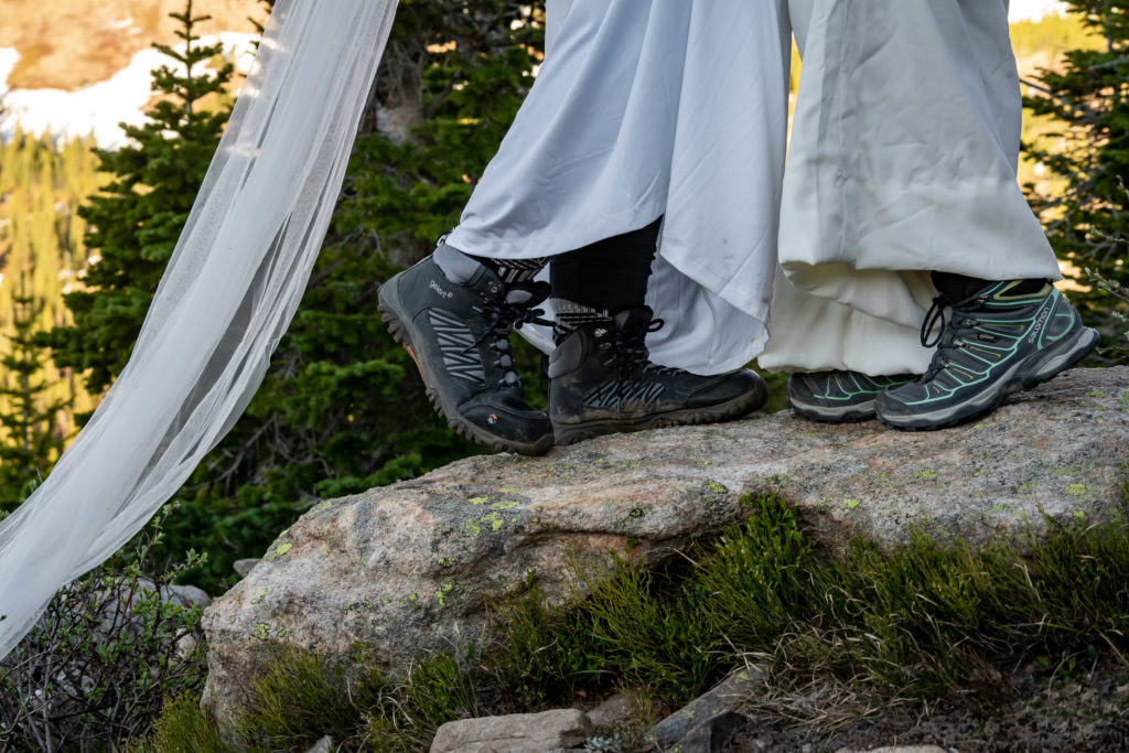 Hiking boots with a wedding dress! Photo by Gabby Jockers Photography. Same sex wedding, lesbian elopement, lesbian wedding, lgbt elopement, lgbtqia wedding, lgbt wedding, colorado elopement, colorado elopement photography, berthoud pass, sunrise elopement, hiking elopement, spring wedding, mountain wedding, adventure photos, mountain elopement, spring elopement, adventure elopement, denver colorado photographer, elopement photographer