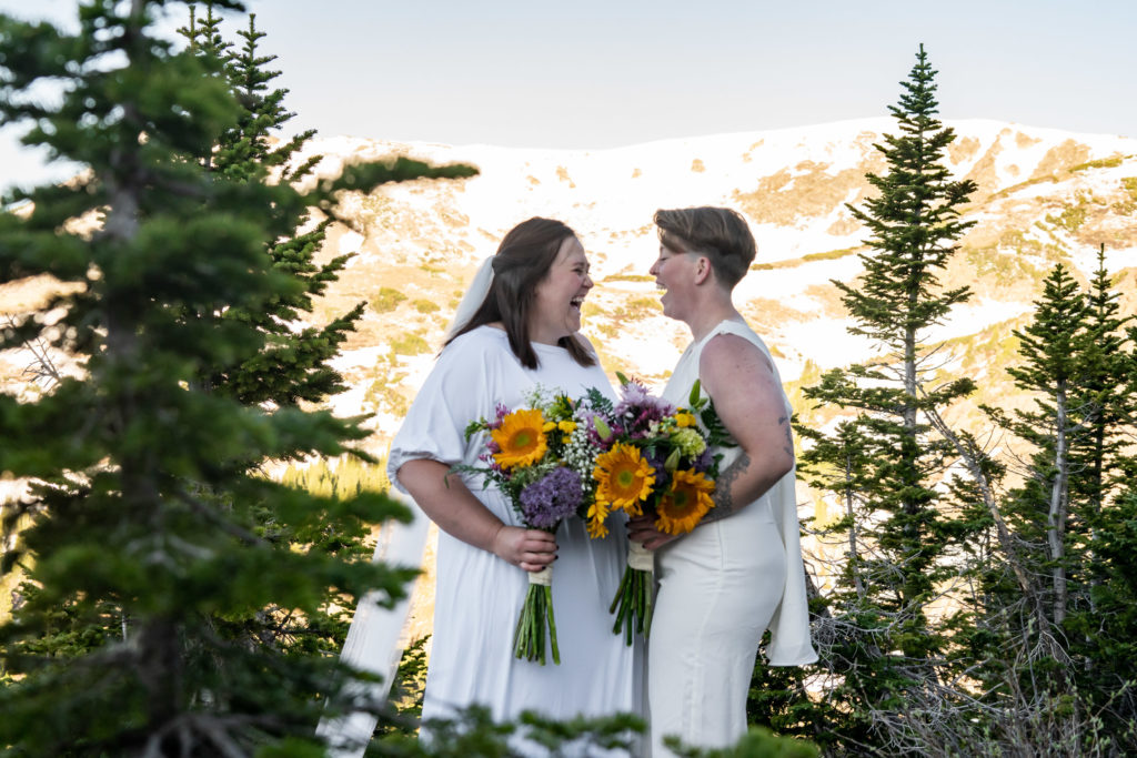 Two brides holding colorful sunflower bouquets in front of a mountain backdrop. Photo by Gabby Jockers Photography. Wedding jumpsuit, Same sex wedding, lesbian elopement, lesbian wedding, lgbt elopement, lgbtqia wedding, lgbt wedding, colorado elopement, colorado elopement photography, berthoud pass, sunrise elopement, hiking elopement, spring wedding, mountain wedding, adventure photos, mountain elopement, spring elopement, adventure elopement, denver colorado photographer, elopement photographer