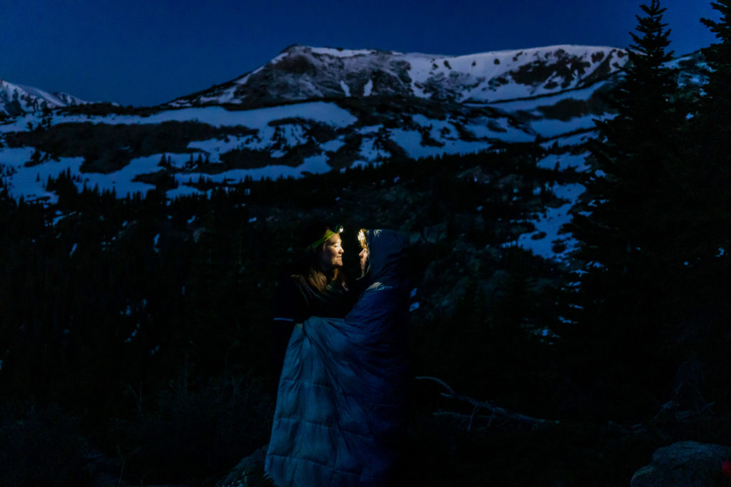Two brides illuminated by their headlamps in front of a snowy mountain before sunrise on their hiking elopement. Photo by Gabby Jockers Photography. Same sex wedding, lesbian elopement, lesbian wedding, lgbt elopement, lgbtqia wedding, lgbt wedding, colorado elopement, colorado elopement photography, berthoud pass, sunrise elopement, hiking elopement, spring wedding, mountain wedding, adventure photos, mountain elopement, spring elopement, adventure elopement, denver colorado photographer, elopement photographer