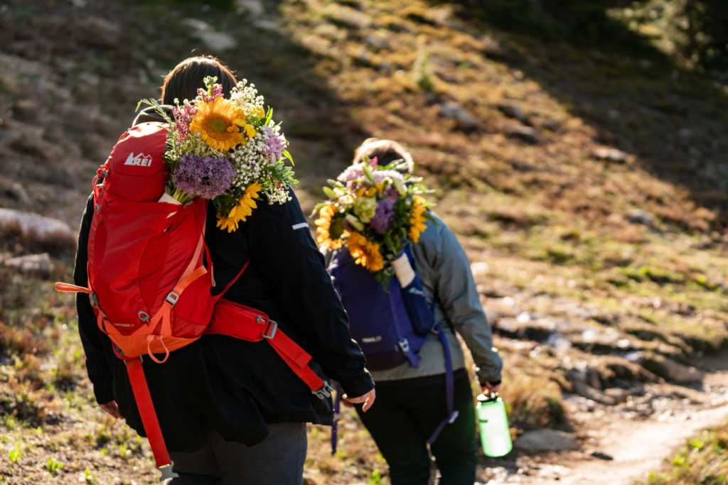 Two brides in their hiking gear with backpack sunflower bouquets on the trail after their sunrise hiking elopement. Photo by Gabby Jockers Photography. Same sex wedding, lesbian elopement, lesbian wedding, lgbt elopement, lgbtqia wedding, lgbt wedding, colorado elopement, colorado elopement photography, berthoud pass, sunrise elopement, hiking elopement, spring wedding, mountain wedding, adventure photos, mountain elopement, spring elopement, adventure elopement, denver colorado photographer, elopement photographer