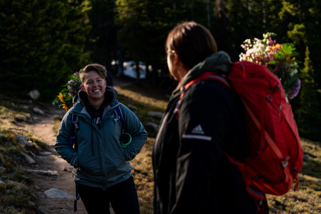 Two brides in their hiking gear with backpack bouquets on the trail after their sunrise hiking elopement. Photo by Gabby Jockers Photography. Same sex wedding, lesbian elopement, lesbian wedding, lgbt elopement, lgbtqia wedding, lgbt wedding, colorado elopement, colorado elopement photography, berthoud pass, sunrise elopement, hiking elopement, spring wedding, mountain wedding, adventure photos, mountain elopement, spring elopement, adventure elopement, denver colorado photographer, elopement photographer