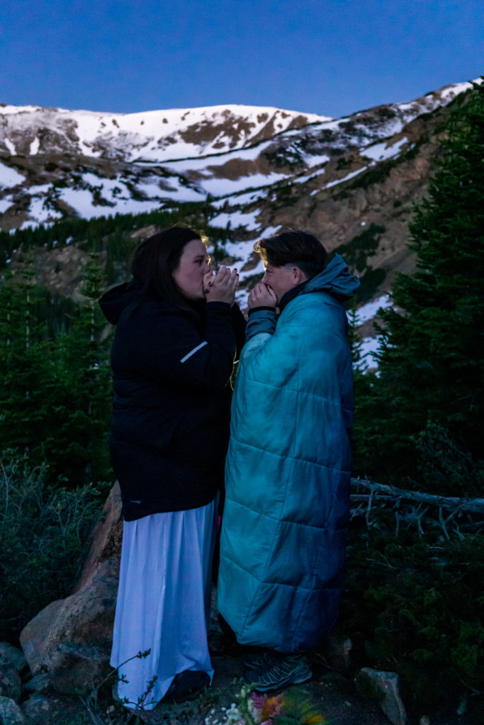 Two brides warming up in front of a mountain alpenglow sunrise. Photo by Gabby Jockers Photography. Same sex wedding, lesbian elopement, lesbian wedding, lgbt elopement, lgbtqia wedding, lgbt wedding, colorado elopement, colorado elopement photography, berthoud pass, sunrise elopement, hiking elopement, spring wedding, mountain wedding, adventure photos, mountain elopement, spring elopement, adventure elopement, denver colorado photographer, elopement photographer
