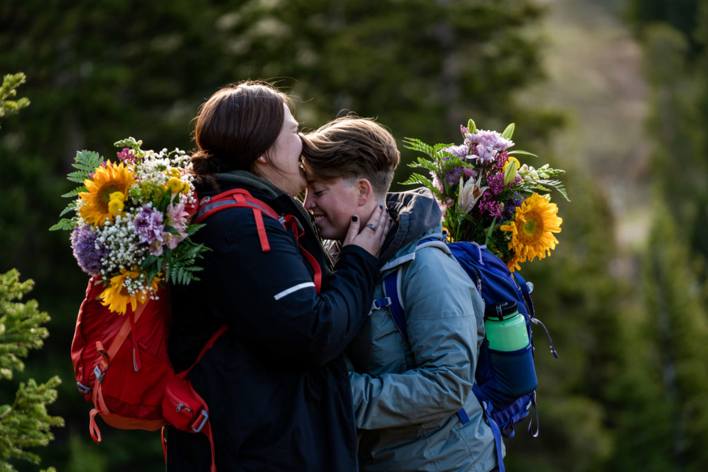 Two brides in their hiking gear with backpack bouquets on the trail after their sunrise hiking elopement. Photo by Gabby Jockers Photography. Wedding jumpsuit, Same sex wedding, lesbian elopement, lesbian wedding, lgbt elopement, lgbtqia wedding, lgbt wedding, colorado elopement, colorado elopement photography, berthoud pass, sunrise elopement, hiking elopement, spring wedding, mountain wedding, adventure photos, mountain elopement, spring elopement, adventure elopement, denver colorado photographer, elopement photographer