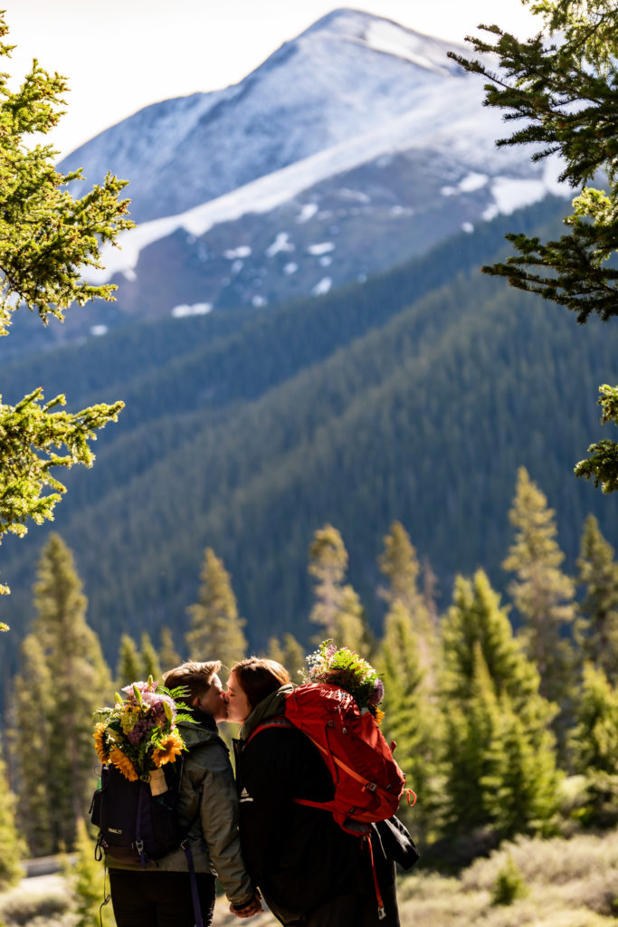 Two brides in hiking gear during their elopement in front of a beautiful Colorado mountain backdrop. Photo by Gabby Jockers Photography. Wedding jumpsuit, Same sex wedding, lesbian elopement, lesbian wedding, lgbt elopement, lgbtqia wedding, lgbt wedding, colorado elopement, colorado elopement photography, berthoud pass, sunrise elopement, hiking elopement, spring wedding, mountain wedding, adventure photos, mountain elopement, spring elopement, adventure elopement, denver colorado photographer, elopement photographer
