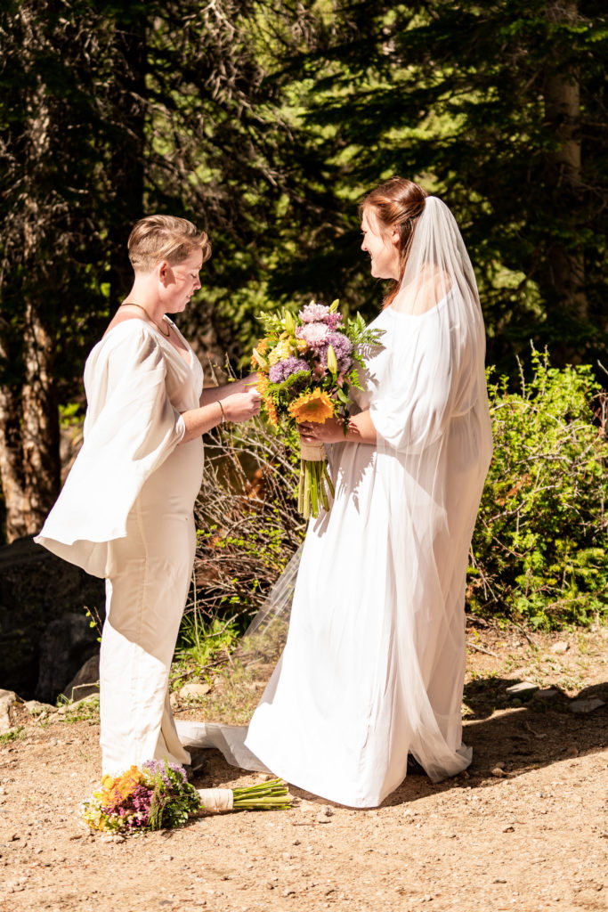 Two brides exchanging vows during a wedding ceremony on their adventurous outdoor elopement. Photo by Gabby Jockers Photography. Wedding jumpsuit, Same sex wedding, lesbian elopement, lesbian wedding, lgbt elopement, lgbtqia wedding, lgbt wedding, colorado elopement, colorado elopement photography, berthoud pass, sunrise elopement, hiking elopement, spring wedding, mountain wedding, adventure photos, mountain elopement, spring elopement, adventure elopement, denver colorado photographer, elopement photographer