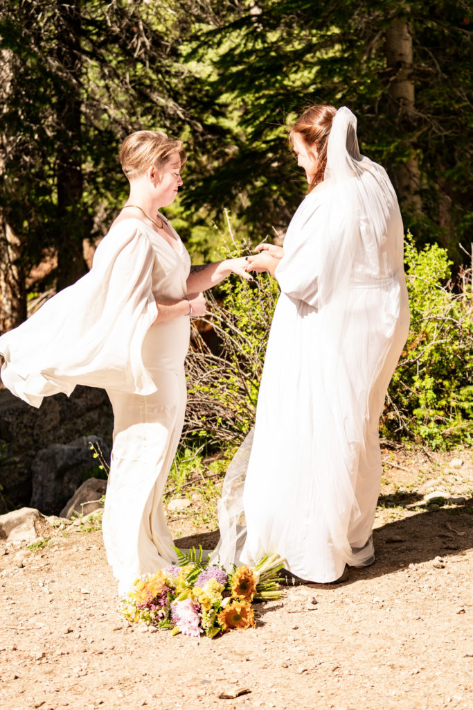 Two brides exchanging rings during a wedding ceremony on their adventurous outdoor elopement. Photo by Gabby Jockers Photography. Wedding jumpsuit, Same sex wedding, lesbian elopement, lesbian wedding, lgbt elopement, lgbtqia wedding, lgbt wedding, colorado elopement, colorado elopement photography, berthoud pass, sunrise elopement, hiking elopement, spring wedding, mountain wedding, adventure photos, mountain elopement, spring elopement, adventure elopement, denver colorado photographer, elopement photographer