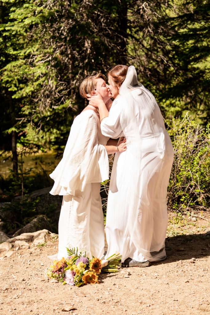 Two brides first kiss after a ceremony with ring exchange. Photo by Gabby Jockers Photography. Wedding jumpsuit, Same sex wedding, lesbian elopement, lesbian wedding, lgbt elopement, lgbtqia wedding, lgbt wedding, colorado elopement, colorado elopement photography, berthoud pass, sunrise elopement, hiking elopement, spring wedding, mountain wedding, adventure photos, mountain elopement, spring elopement, adventure elopement, denver colorado photographer, elopement photographer
