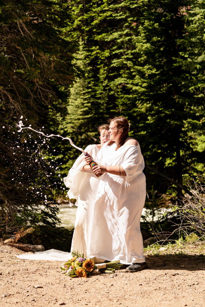Two brides popping champagne to celebrate their wedding! Photo by Gabby Jockers Photography. Wedding jumpsuit, Same sex wedding, lesbian elopement, lesbian wedding, lgbt elopement, lgbtqia wedding, lgbt wedding, colorado elopement, colorado elopement photography, berthoud pass, sunrise elopement, hiking elopement, spring wedding, mountain wedding, adventure photos, mountain elopement, spring elopement, adventure elopement, denver colorado photographer, elopement photographer