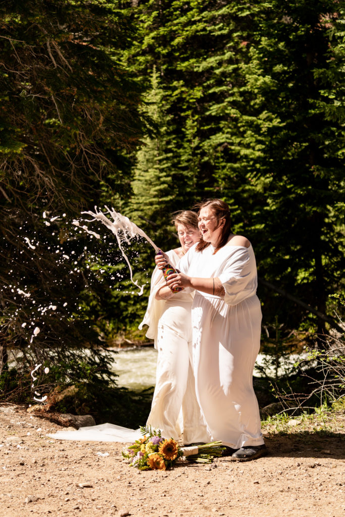 Two brides celebrating their wedding by popping a bottle of pride champagne. Photo by Gabby Jockers Photography. Wedding jumpsuit, Photo by Gabby Jockers Photography. Same sex wedding, lesbian elopement, lesbian wedding, lgbt elopement, lgbtqia wedding, lgbt wedding, colorado elopement, colorado elopement photography, berthoud pass, sunrise elopement, hiking elopement, spring wedding, mountain wedding, adventure photos, mountain elopement, spring elopement, adventure elopement, denver colorado photographer, elopement photographer