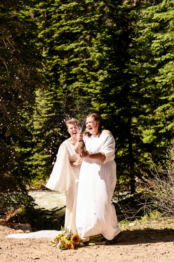 Two brides celebrating their wedding by popping a bottle of pride champagne. Photo by Gabby Jockers Photography. Wedding jumpsuit, Same sex wedding, lesbian elopement, lesbian wedding, lgbt elopement, lgbtqia wedding, lgbt wedding, colorado elopement, colorado elopement photography, berthoud pass, sunrise elopement, hiking elopement, spring wedding, mountain wedding, adventure photos, mountain elopement, spring elopement, adventure elopement, denver colorado photographer, elopement photographer