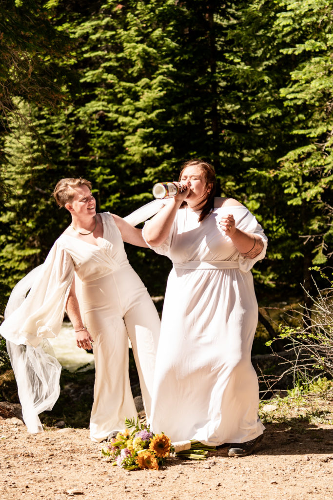 Two brides celebrating their wedding with a bottle of pride champagne and sunflower bouquet. Photo by Gabby Jockers Photography. Wedding jumpsuit, Same sex wedding, lesbian elopement, lesbian wedding, lgbt elopement, lgbtqia wedding, lgbt wedding, colorado elopement, colorado elopement photography, berthoud pass, sunrise elopement, hiking elopement, spring wedding, mountain wedding, adventure photos, mountain elopement, spring elopement, adventure elopement, denver colorado photographer, elopement photographer