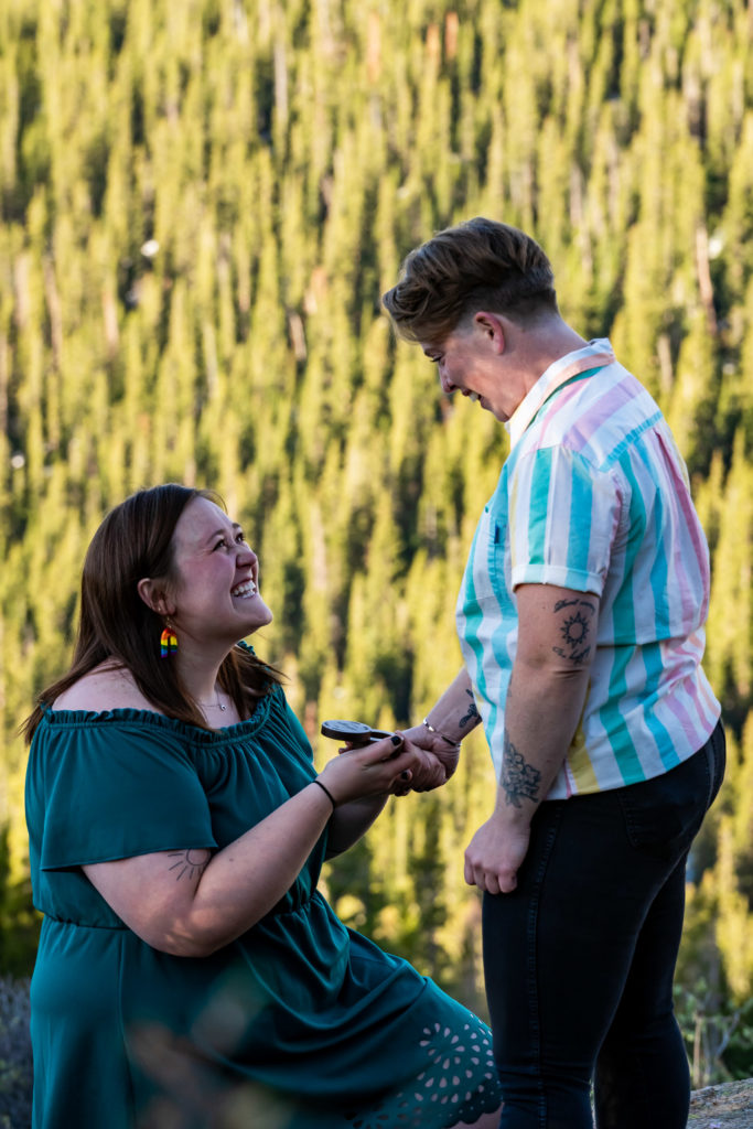 One woman her knee proposing jubilantly to her girlfriend. Photo by Gabby Jockers Photography. Lgbt proposal, hiking proposal, Same sex wedding, lesbian elopement, lesbian wedding, lgbt elopement, lgbtqia wedding, lgbt wedding, colorado elopement, colorado elopement photography, berthoud pass, sunrise elopement, hiking elopement, spring wedding, mountain wedding, adventure photos, mountain elopement, spring elopement, adventure elopement, denver colorado photographer, elopement photographer