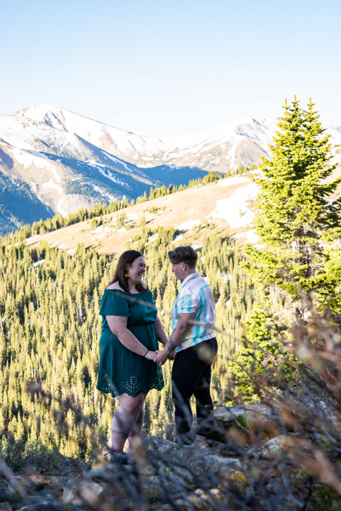 Two women holding hands in front of a mountain backdrop after a hiking proposal. Photo by Gabby Jockers Photography. Lgbt proposal, Same sex wedding, lesbian elopement, lesbian wedding, lgbt elopement, lgbtqia wedding, lgbt wedding, colorado elopement, colorado elopement photography, berthoud pass, sunrise elopement, hiking elopement, spring wedding, mountain wedding, adventure photos, mountain elopement, spring elopement, adventure elopement, denver colorado photographer, elopement photographer