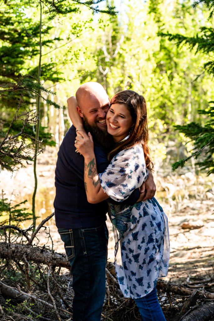 A newly engaged couple laughing together in front of a sunny lake. Photo by Gabby Jockers Photography. colorado engagement photography, colorado engagement photos, colorado engagement session, brainard lake engagement photos, brainard lake engagement session, colorado photography, brainard lake engagement photos, mountain engagement photos, lake engagement photos, mountain engagement session, hiking engagement, adventure photos, adventure session, couples photos, morning engagement photos