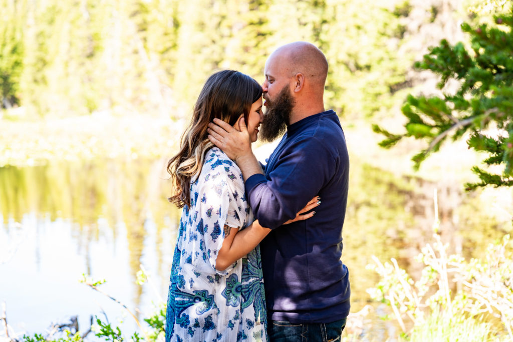 A man kissing the forehead of his fiance as they embrace in front of a sunny lake. Photo by Gabby Jockers Photography. colorado engagement photography, colorado engagement photos, colorado engagement session, brainard lake engagement photos, brainard lake engagement session, colorado photography, brainard lake engagement photos, mountain engagement photos, lake engagement photos, mountain engagement session, hiking engagement, adventure photos, adventure session, couples photos, morning engagement photos