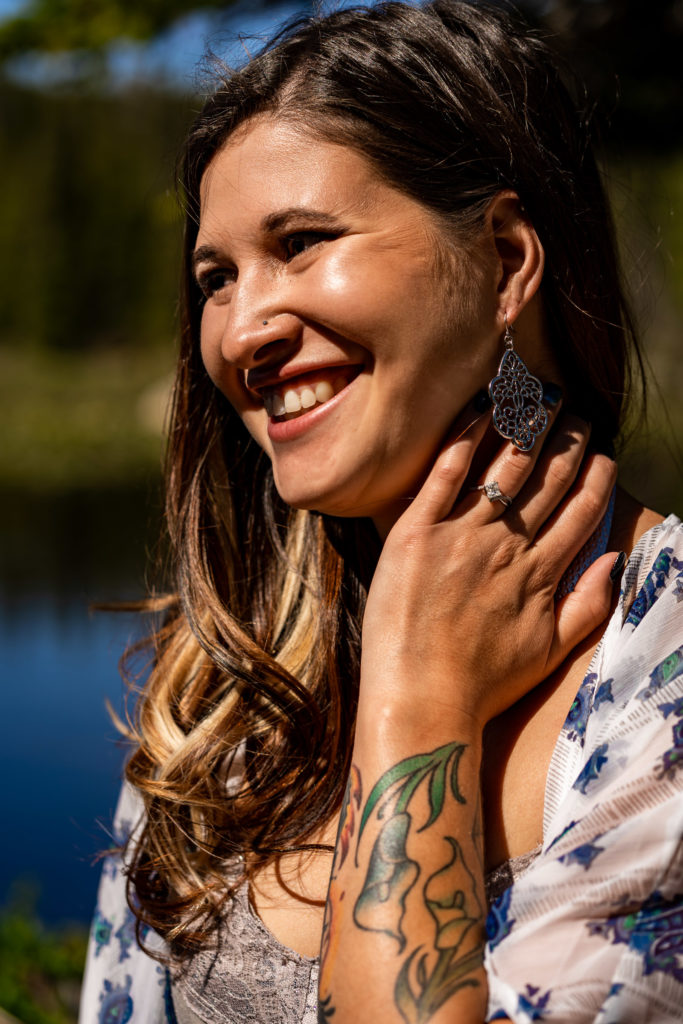 A radiant smiling woman with cool tattoos and beautiful jewelry. Photo by Gabby Jockers Photography. colorado engagement photography, colorado engagement photos, colorado engagement session, brainard lake engagement photos, brainard lake engagement session, colorado photography, brainard lake engagement photos, mountain engagement photos, lake engagement photos, mountain engagement session, hiking engagement, adventure photos, adventure session, couples photos, morning engagement photos