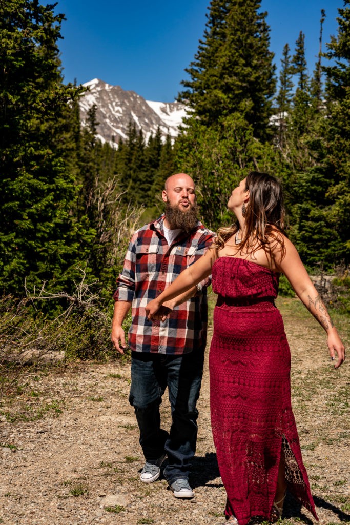 A silly couple holding hands and making kissy faces at each other while walking down a trail. Photo by Gabby Jockers Photography. colorado engagement photography, colorado engagement photos, colorado engagement session, brainard lake engagement photos, brainard lake engagement session, colorado photography, brainard lake engagement photos, mountain engagement photos, lake engagement photos, mountain engagement session, hiking engagement, adventure photos, adventure session, couples photos, morning engagement photos